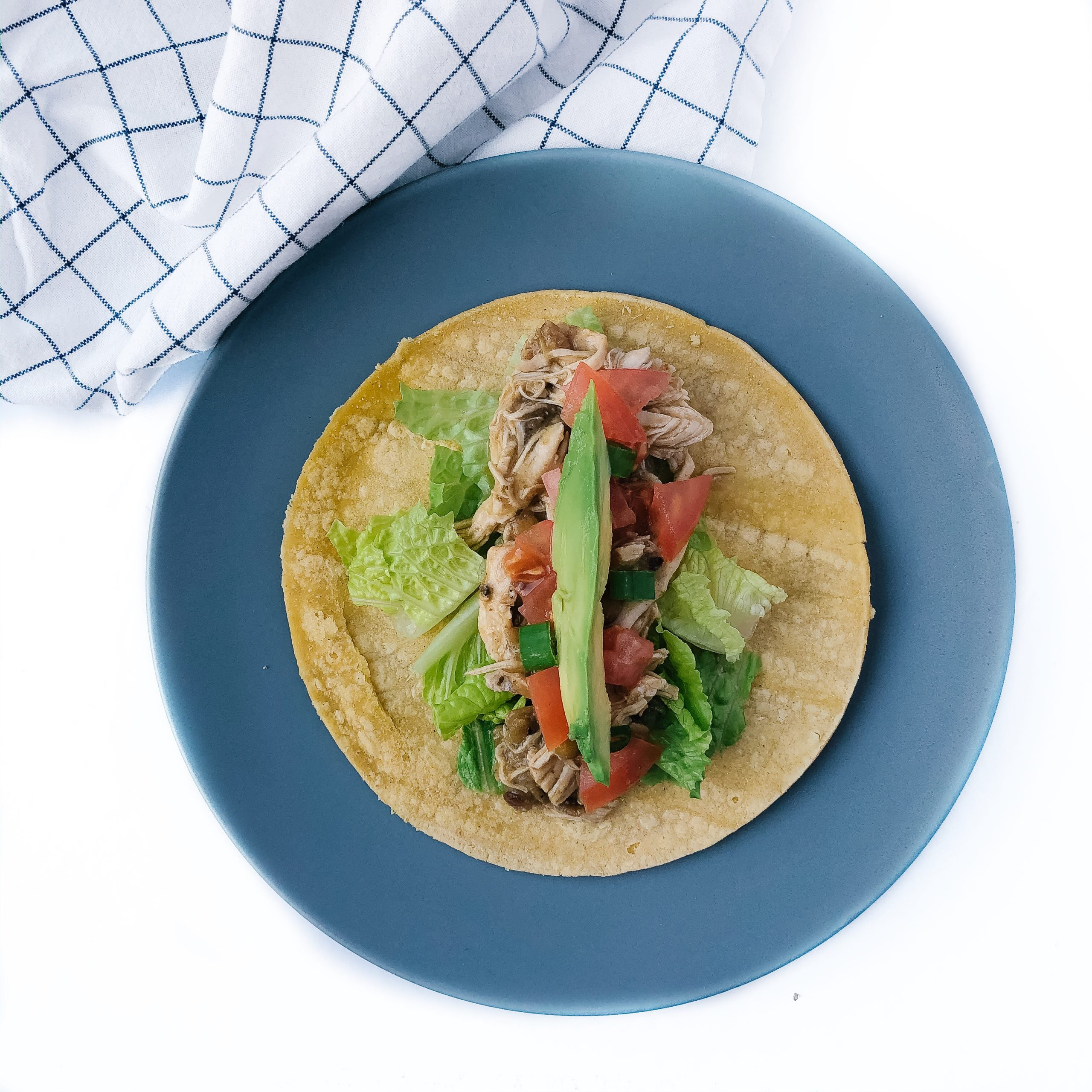 chicken and lentil tacos assembled on a blue plate with lettuce, tomato, avocado topping