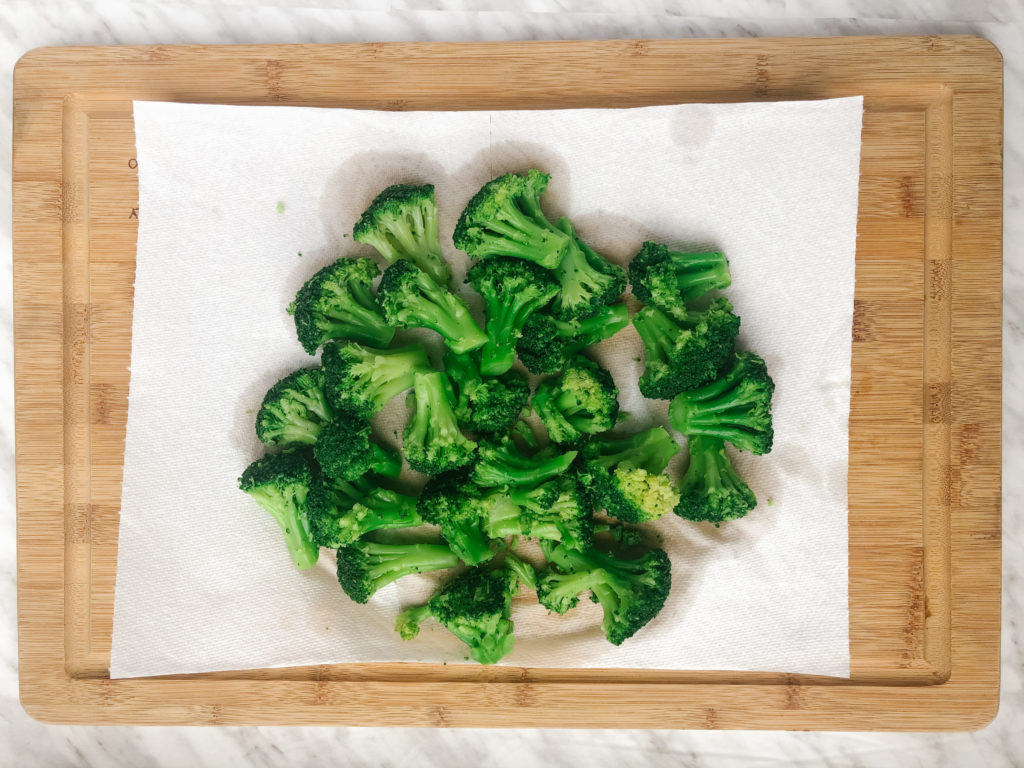 Thawed frozen broccoli on a paper towel