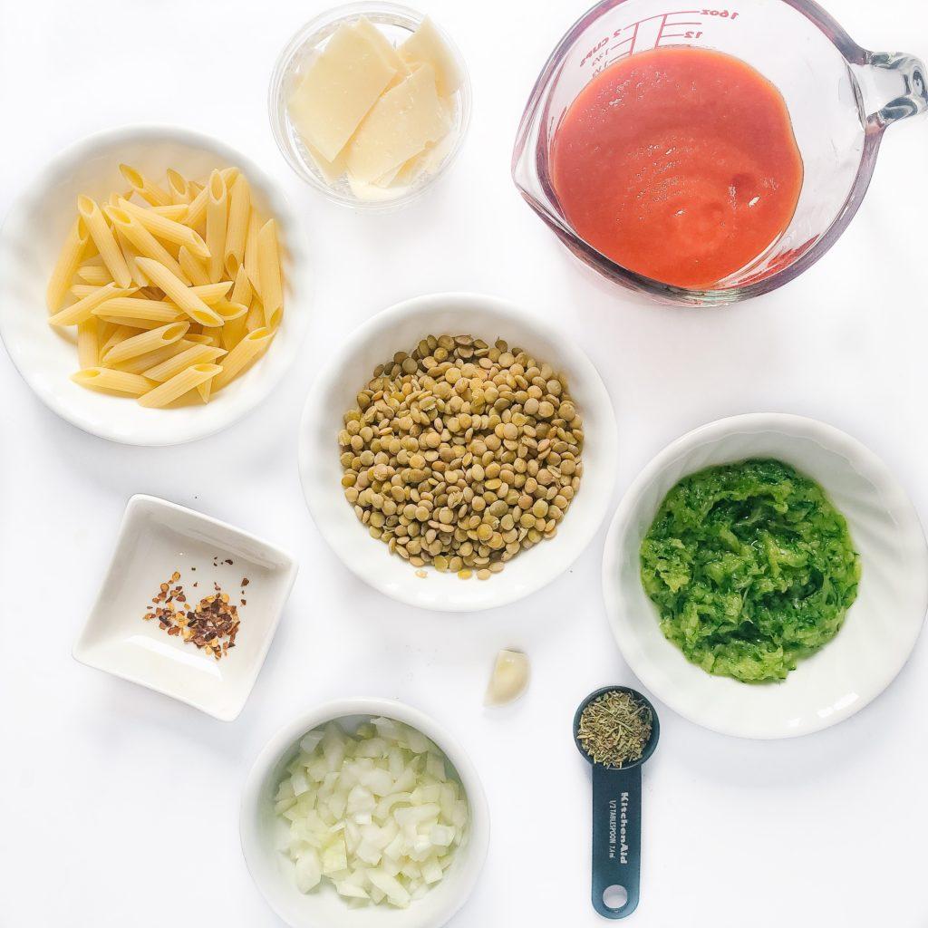 Recipe ingredients - pasta, lentils, chili flakes, onion, Italian seasoning, parmesan cheese, passata, garlic, shredded zucchini, passata