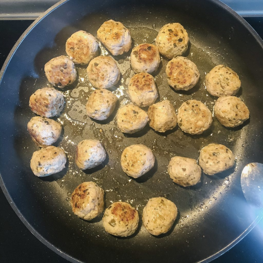 pesto chicken meatballs cooking in pan with oil
