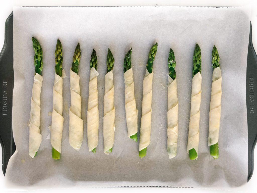 lemon parmesan phyllo wrapped asparagus on a sheet pan before baking
