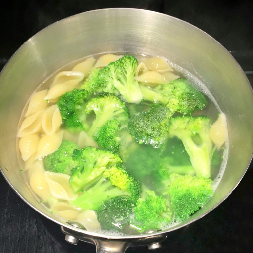 pasta and frozen broccoli in boiling water