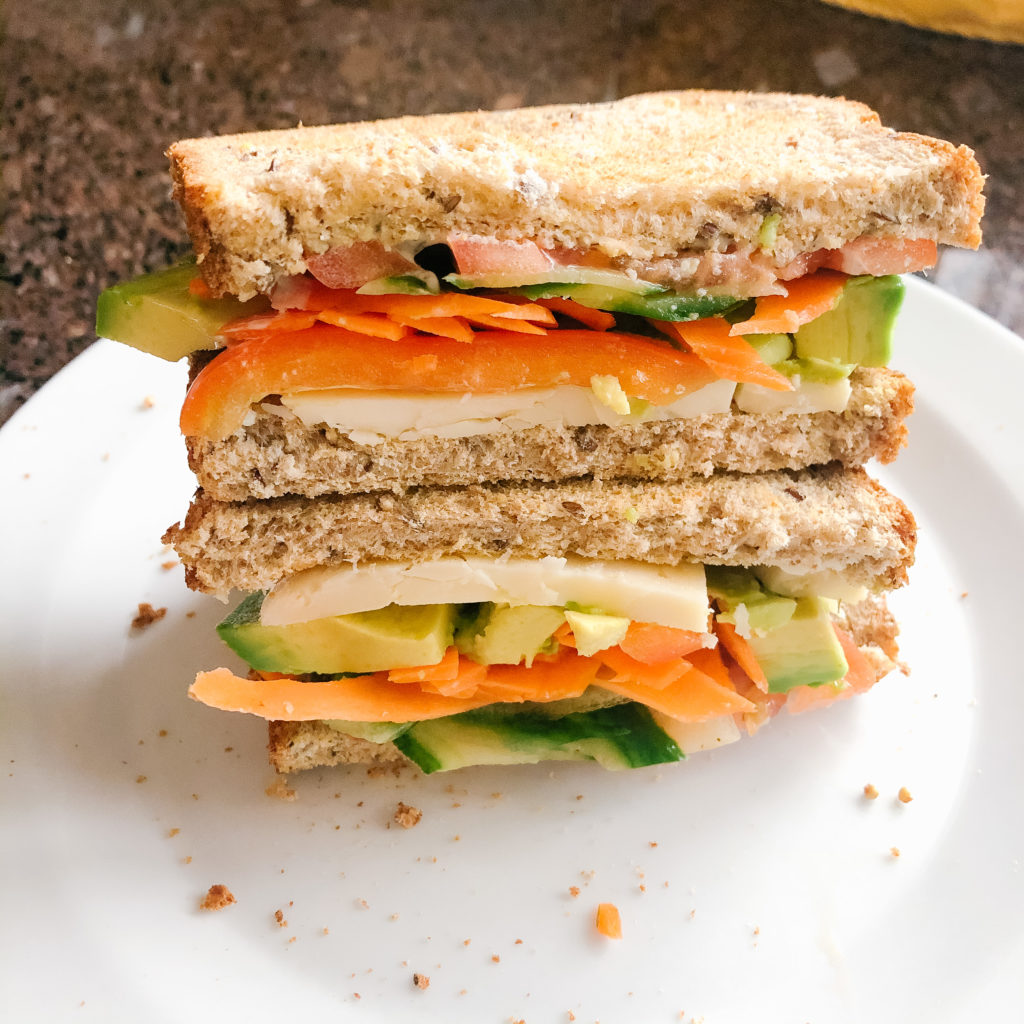 easy veggie loaded sandwich stacked on a white plate